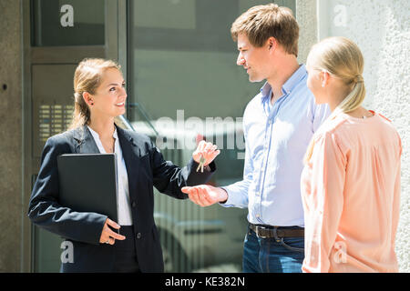 Smiling Female Real Estate Agent Giving House Key To Young Couple - Stock Photo
