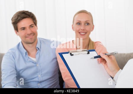 Close-up Of Consultant With Clipboard In Front Of Happy Young Couple - Stock Photo