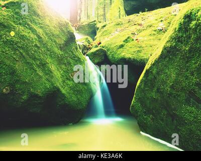 Weir in mountain stream. Colorful leaves  on stones into water. Dark green mossy boulders. - Stock Photo