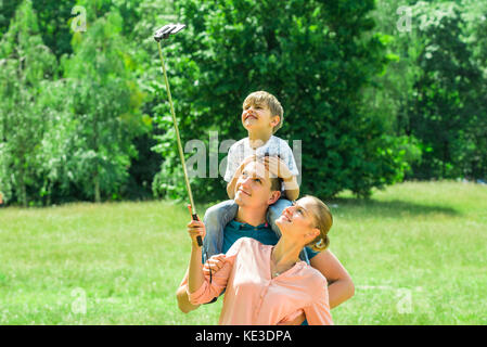 Smiling Young Family Taking Selfie In Park - Stock Photo