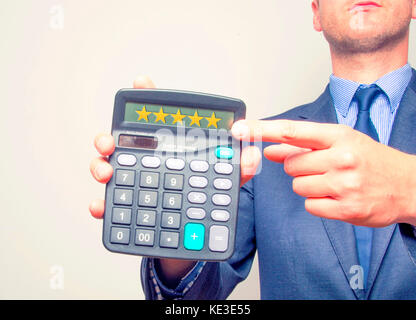 Young businessman pointing on calculator.Five Stars Sign. Taxes business concept. Good Price - Stock Photo