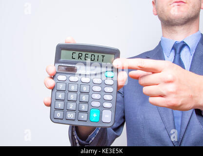 Young businessman pointing on calculator. Taxes business concept Calculator with CREDIT on display white background. - Stock Photo