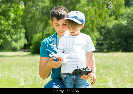 Father And Son Playing With The White Drone In The Park - Stock Photo