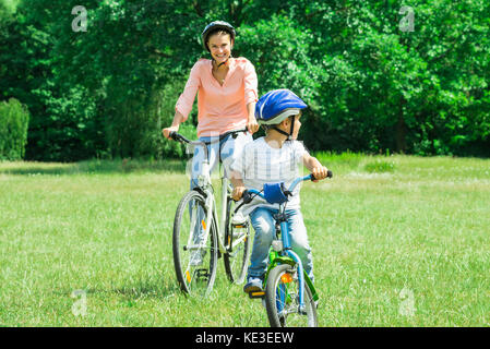 Mother And Son Enjoying The Ride On Bicycle In The Park - Stock Photo
