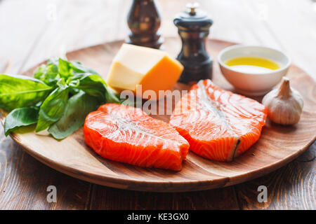 Salmon steaks with cheese and fresh ingredients - Stock Photo