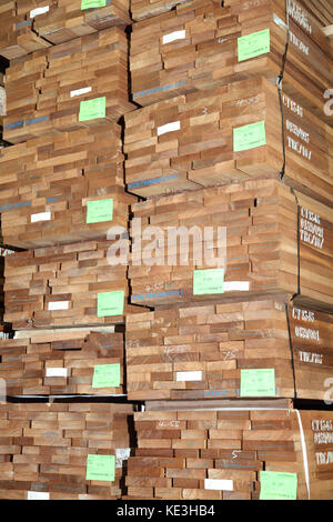 Imported hardwood timber planks stacked in a modern, UK distribution warehouse. - Stock Photo
