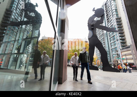 Seattle, United States. 18th Oct, 2017. Seattle, Washington: Couple walks by the Hammering Man at the Seattle Art - Stock Photo
