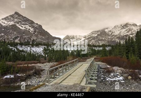 Hiking and Equestrian Wood Bridge over Kananaskis Country Sheep River in Alberta Foothills and dramatic cloudy sky - Stock Photo