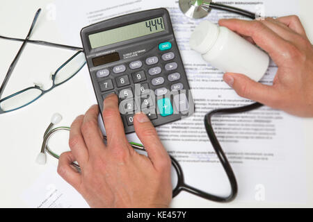 Healthcare costs and fees concept.Hand of smart doctor used a calculator for medical costs in modern hospital with - Stock Photo