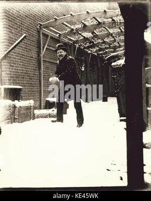 Unidentified man making a snowball behind a brick building - Stock Photo