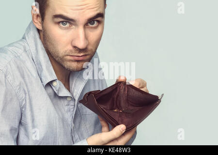 Bussinessman holding an empty wallet in his hands. The guy shows the lack of money - Stock Photo