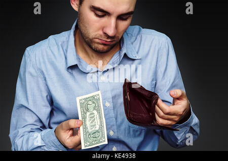 a sad young man shows that he has in the wallet a one dollar. Hands close-up holding one dollar and a leather purse. - Stock Photo