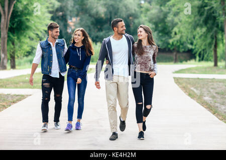 Two beautiful young lovers couple walking in summer park. full-length portrait of happy smiling attractive people - Stock Photo