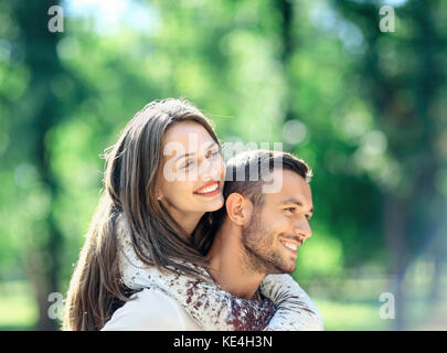 Loving couple man and woman having fun piggybacking in park. Happy smiling boyfriend and girlfriend enjoying each - Stock Photo