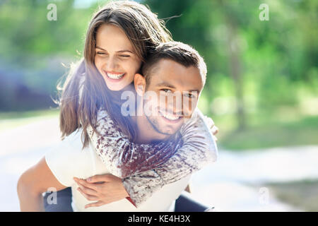Man carrying his girlfriend on the back. Happy laughing couple piggyback. Young cheerful loving pair have fun together - Stock Photo
