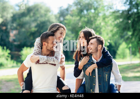 Two loving couples piggyback having fun outdoors. Girls sitting on back of guys smiling. Young women and men playing - Stock Photo