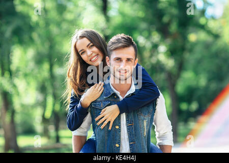 Girl rides on back of guy, smiling at camera outdoors. Loving couple piggyback in nature in park. Two young people - Stock Photo