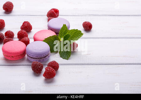 Closeup view of macaroons with raspberries with mint over white wooden background. Place or space for text - Stock Photo