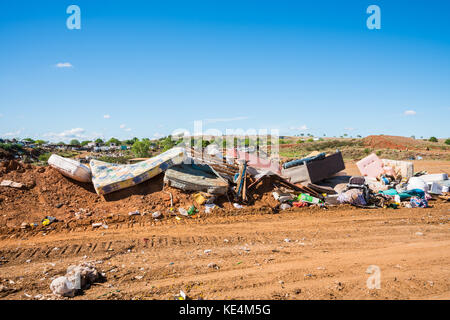 Household goods on rubbish heap at refuse collection site - Stock Photo