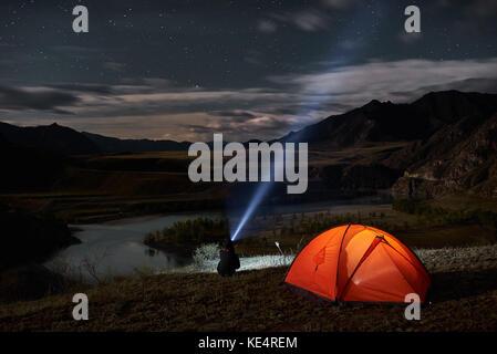 Man tourist with flashlight near his camp tent at night. - Stock Photo