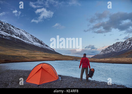 Hiker stand at camping in the mountains during springtime. - Stock Photo