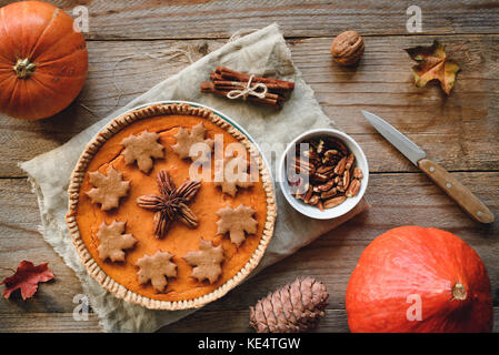 Autumn pumpkin pie with pecan nuts and gingerbread spice cookies on wooden table. Table top view - Stock Photo
