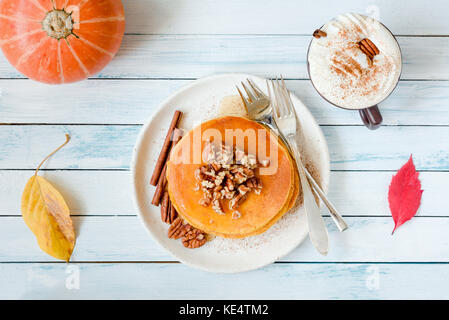 Pumpkin pancakes with pecan nuts, honey and cup of coffee. Autumn food composition on white table. Top view, flat - Stock Photo