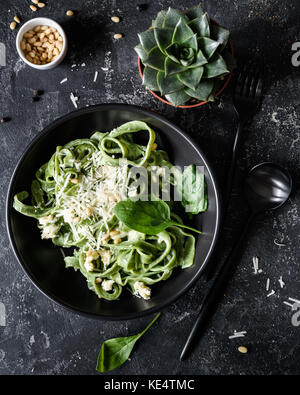 Green spinach pasta with cheese and pine nuts in a black bowl with black cutlery. Gourmet italian meal. Top view - Stock Photo