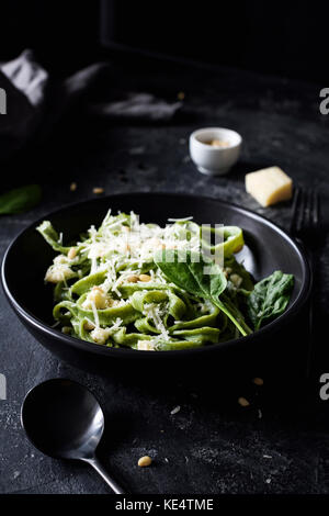 Green spinach pasta with cheese and pine nuts in a black bowl with black cutlery. Gourmet italian meal. Side view - Stock Photo