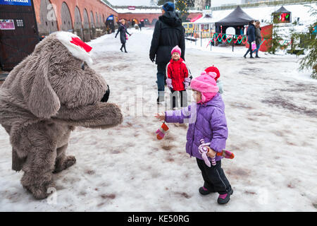 Hamina, Finland - December 13, 2014: Christmas fair in Hamina bastion, animators in animal costumes dance with children - Stock Photo