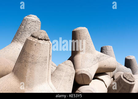 Man made concrete blocks, tetrapods, act as seawall defence around a harbour wall. Crete, Greece, 2017 - Stock Photo