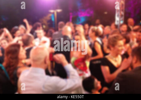 Blurred background with people in a night dancing party - Stock Photo