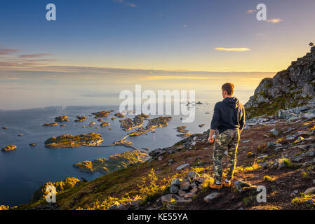 Hiker standing at the top of mount Festvagtinden on Lofoten islands in Norway - Stock Photo