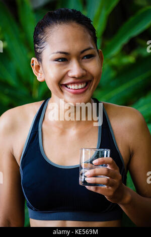 Asian woman in fitness clothes with a glass of water smiling - Stock Photo