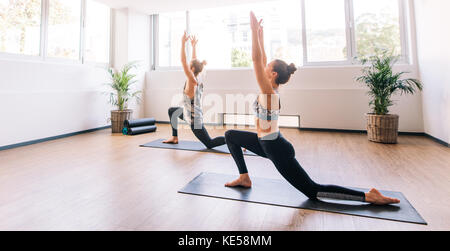 Two young people working out indoors. Fitness class doing yoga.  Man and woman stretching forward in warrior pose. - Stock Photo