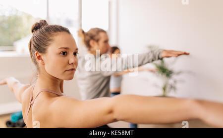Fitness people doing yoga. Women exercising at yoga class. Virabhadrasana pose. - Stock Photo