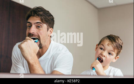 Father and son brushing teeth in bathroom. Young man with his son together brushing teeth and looking in mirror. - Stock Photo