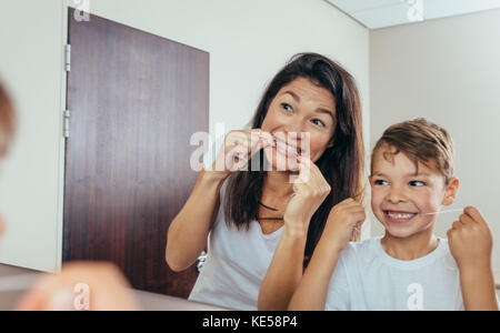 Little boy with his mother in bathroom cleaning teeth with dental floss. Woman with son looking in mirror and cleaning - Stock Photo