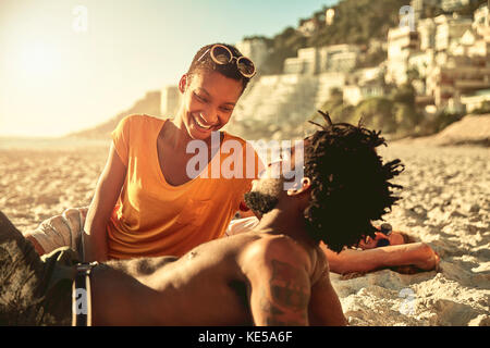 Playful young couple relaxing on sunny summer beach - Stock Photo