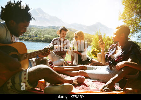 Young friends hanging out, playing guitar and enjoying picnic at sunny summer riverside - Stock Photo