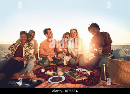 Portrait young friends hanging out, enjoying picnic on sunny summer beach - Stock Photo