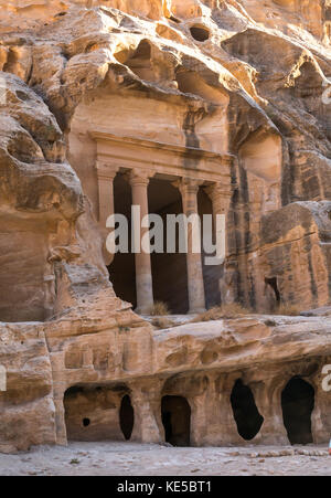 Nabataean Triclinium ruin carved in red sandstone cliff, Little Petra gorge, Siq al-Barid, archaeological site, - Stock Photo