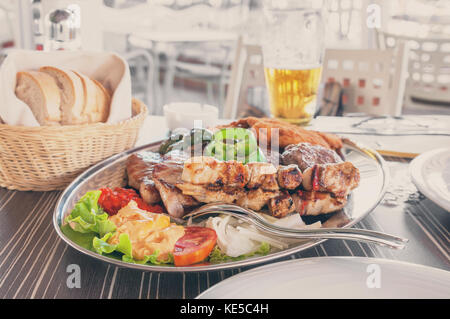 meat beef pork chicken and Turkey with vegetables on a large platter with French fries, peppers, tomatoes, eggplant, - Stock Photo