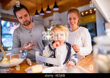 Young family making cookies at home. - Stock Photo