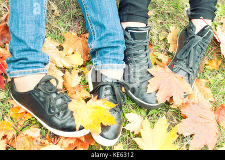 Two girls shoes on autumn leaves, top view, toned photo