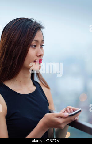Young Asian Woman on her Cell Phone - Stock Photo
