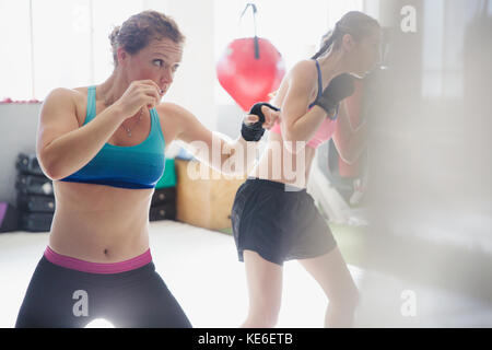 Determined female boxers shadowboxing in gym - Stock Photo