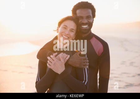 Portrait smiling, affectionate couple hugging on sunset summer beach - Stock Photo