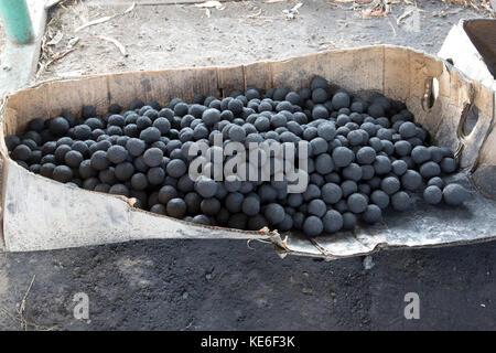 Briquette balls for African stoves made from charcoal dust in drying racks Restart Africa Gilgil Kenya - Stock Photo