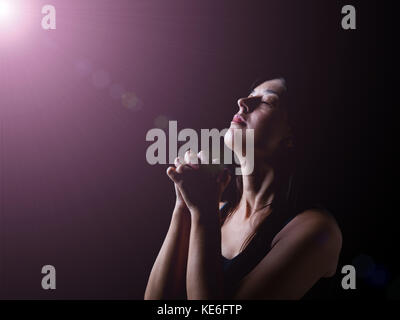 Faithful woman praying under a divine or celestial light and feeling the presence or being touched by god. Hands - Stock Photo